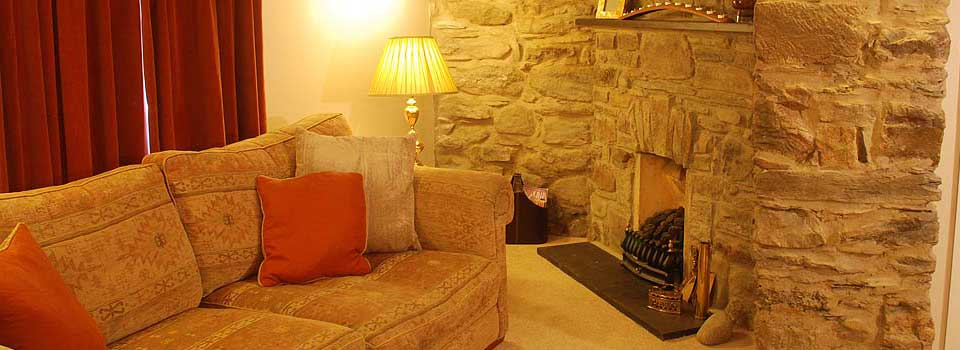 The cosy lounge with stone inglenook fireplace.